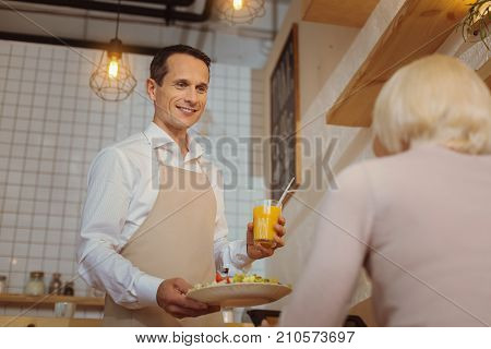 Your breakfast. Handsome nice polite waiter holding breakfast and looking at his customer while serving it in the cafe