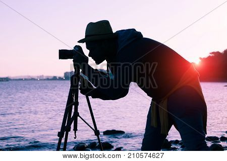 Silhouette of photographer at sunset on the beach using camera on tripod - Man taking picture in low brightness conditions standing by the ocean - Concept of travel hobby and photography equipment