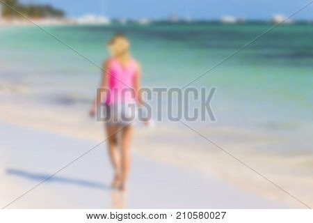 Blurred tropical background. Blurred Young woman walking on perfect tropical beach and turquoise ocean water Romantic seashore blue sea and coco palm trees
