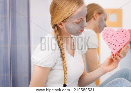 Woman Having Grey Face Mask Holding Heart Sponge