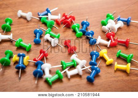 Set of push pins in different colors on a wooden background