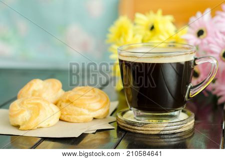 Breakfast, cup of hot black coffee and choux