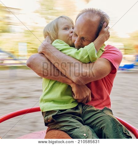 Little boy embracing and kissing his father while riding on carousel. Toned image with a square ratio