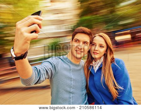 Beautiful young couple taking photos with mobile. Toned image with a square ratio
