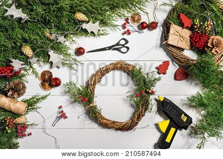 Make a Christmas wreath with your own hands. Spruce branch, Christmas wreath and gifts on a white wooden background. Workplace for preparing handmade decorations. Christmas and New year