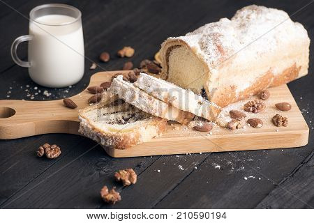 Sliced homemade sponge cake filled with poppy seeds walnuts and almonds displayed on a wooden trencher with a glass of milk near on a rustic wooden table