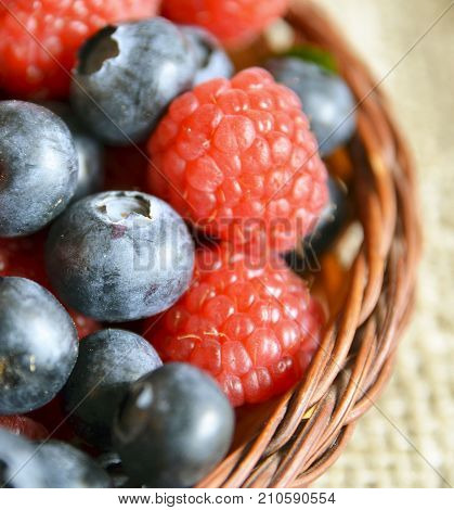 Fresh organic blueberries and raspberries close up.Freshly picked raspberries and blueberries in a basket.Blueberry and raspberry.Healthy eating,diet concept.Selective focus.