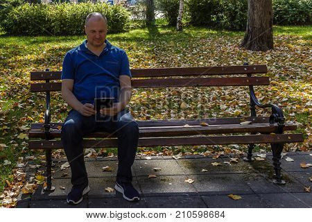 Man in blue shirt reading with digital tablet on a park bench on a sunny day
