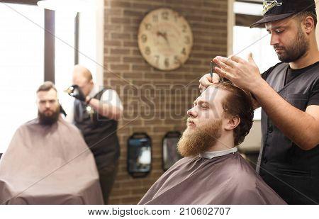 Barbershop for men. Young barber beard with scissors at barbershop
