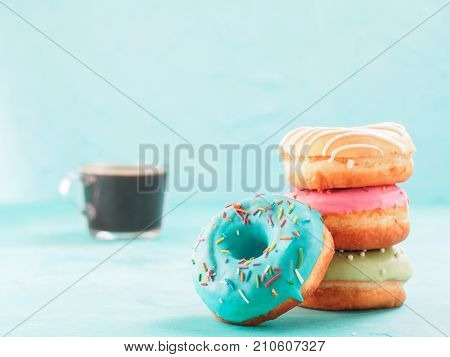 Donuts and coffee on blue concrete background with copy space. Colorful donuts and coffee cup with copyspace. Glazed doughnuts in stack on foreground and coffee on background