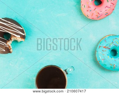 Top view of assorted donuts and coffee on blue concrete background with copy space. Colorful donuts and coffee background. Various glazed doughnuts with sprinkles.