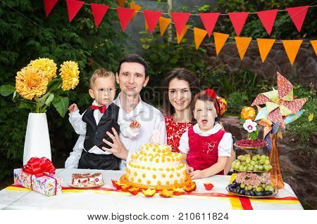 A family of four people is sitting at a festive table with a cake and gifts. Bad boring children's holiday. Emotion of boredom disappointment