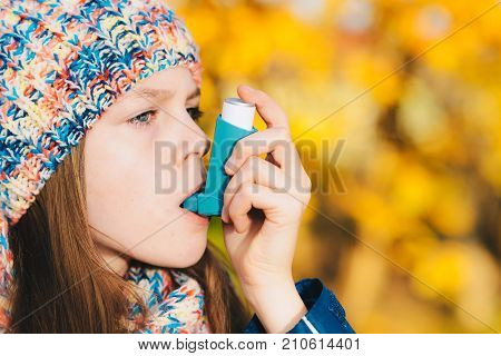 Asthma patient girl inhaling medication for treating shortness of breath and wheezing in a park. Chronic disease control allergy induced asthma remedy and allergy disease concept