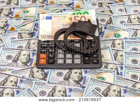 Steel police handcuffs euro banknotes and calculator lying on the background of american dollars
