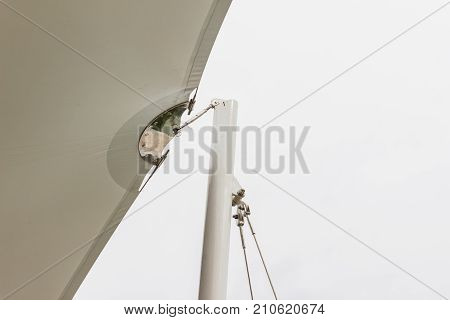 Construction details : Stainless steel support to round steel post of roof canvas with white sky background