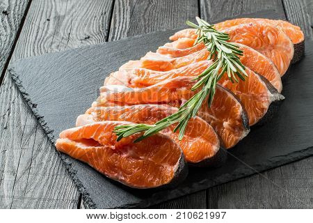 Fresh salmon sliced on steaks and rosemary on slate plate. Preparation for cooking fish. Salmon is source of protein Omega-Z and vitamin D. Important product in diet and healthy nutrition