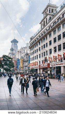 Shanghai, China - Nov 6, 2016: On Nanjing Road Pedestrian Street - Modern buildings in western architectural designs line the metropolitan area. People walking on street.