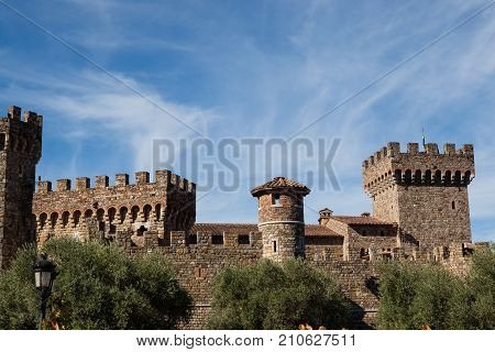 NAPA VALLEY CALIFORNIA - November 8 2016 : Castello di Amorosa's turrets rising above large olive trees on November 8 2016 in Napa Valley California.