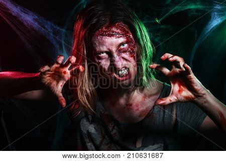 Close-up portrait of horrible zombie woman with wounds. Horror. Halloween poster. The shouting female zombie