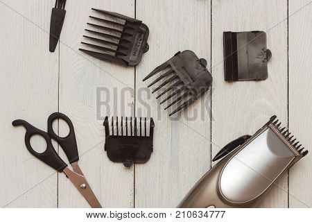 Stylish Professional Barber Clippers, Hair Clippers, Haircut accessories on wood background