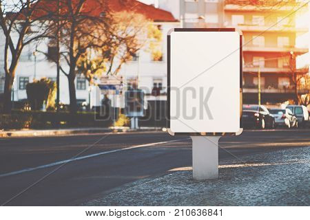Vertical city blank information banner standing near road on paving stone; empty mock-up of urban poster next to highway; white clear billboard with copy space place for logo text or advertising