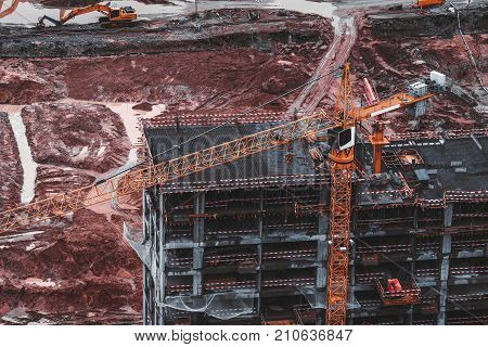 Orange modern crane lifting construction cargo to unfinished house on dull moody day in a huge pit full of reddish dirt and other construction machinery such as excavators generators cement feeder