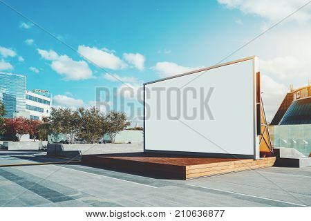 Contemporary wooden stage in urban settings with blank information LCD screen or banner; empty mock-up of poster; white clean billboard with copy space zone for logo text or advertising caption