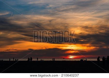 Sunset on Lake Erie with boat and beachgoer silhouettes