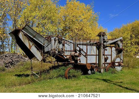 An old threshing machine is left parked in a grove of autumn colored leaves and trees.