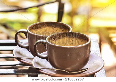 Coffee Cup With Froth On Table In Morning Light