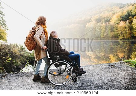 Active senior couple on a walk in a beautiful autumn nature. A woman and man in a wheelchair by the lake in the early morning.