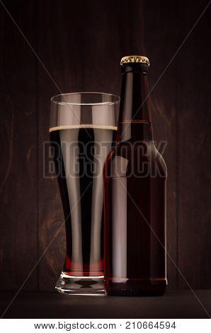 Brown beer longneck bottle and glass weizen with porter on dark wood board vertical mock up. Template for advertising design branding identity.