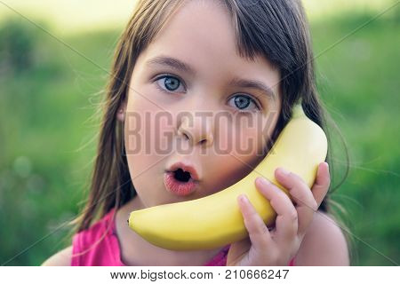 Little caucasian girl honing with a banana on the nature background.