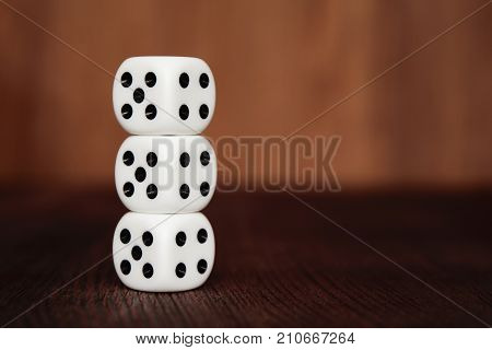 Three white plastic dices on each other on brown wooden board background. Six sides cube with black dots. Number 4 and 5.