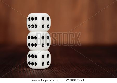 Three white plastic dices on each other on brown wooden board background. Six sides cube with black dots. Number 4 and 6.