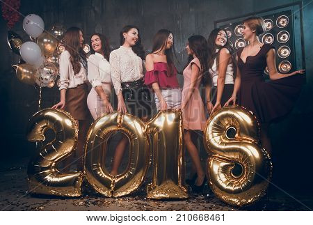 Beautiful girls communicate with each other and happy smiling. Christmas party in the club with gold balloons numbers 2018. Christmas party. Hew year 2018.
