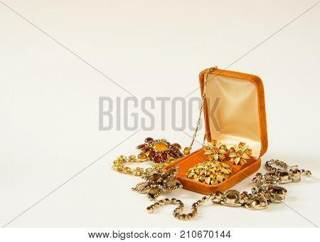 Woman's Jewelry. Vintage jewelry background. Beautiful bright rhinestone brooches and necklace in a jewelry box on white background. Flat lay top view with copy space
