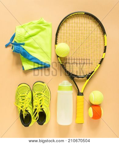 Tennis stuff on cream background. Sport fitness tennis healthy lifestyle sport stuff. Tennis racket lime trainers tennis ball lime athletic shorts sports bottle. Flat lay top view
