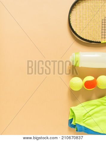 Kids tennis stuff on cream background. Sport, fitness, tennis, healthy lifestyle, sport stuff. Lime trainers, tennis balls, lime athletic shorts, sports bottle. Flat lay top view