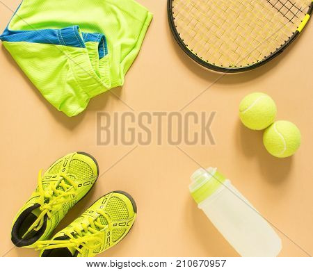 Kids tennis stuff on cream background. Sport, fitness, tennis, healthy lifestyle, sport stuff. Tennis racket, lime trainers, tennis ball, lime athletic shorts, sports bottle. Flat lay top view
