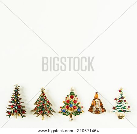 Xmas theme. Woman's Jewelry. Vintage jewelry background. Beautiful bright rhinestone christmas tree brooches on white background. Flat lay, top view with copy space
