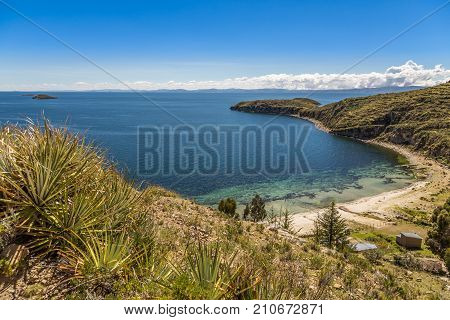 Blue water coast of Titicaca lake and white sand beach at Incas Island of the Sun Bolivia south America