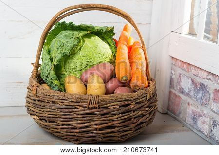 basket with raw vegetables for cooking a french Pot-au-feu