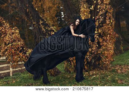 Witch black widow Queen hugs her black horse in a horror dark forest