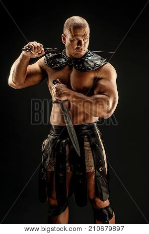 Severe barbarian in leather costume with two swords. Portrait of balded muscular gladiator. Studio shot. Black background.