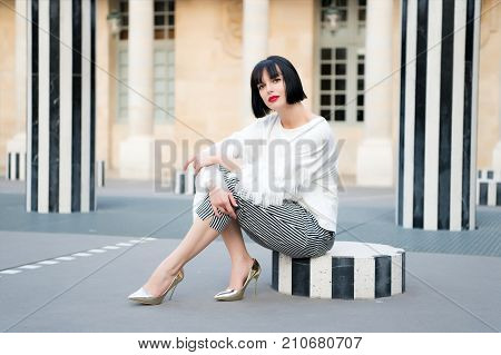 Woman With Brunette Hair Sit At Street Stripped Column.