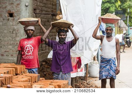 PONDICHERY PUDUCHERY INDIA - September 02 2017. Unidentified indian men have bricks in a plate on their head for the house construction. Concept of manual labor very hard.