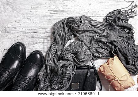 Flat-lay of autumn lady' s clothes. Black handbag, gray scarf and oxford leather boots on white wooden background, top view