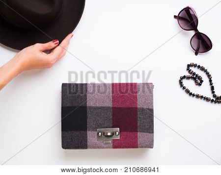 Flat lay with lady's hat, sun glasses necklace and clutch. Autumn colours accessories clothes on white background. Woman's hand