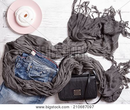 Flat-lay of autumn lady' s clothes. Blue denim jeans, black handbag, gray scarf, oxford leather boots and plate with cake on white wooden background, top view